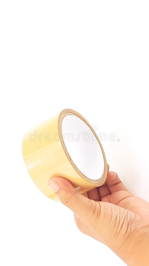 Man hand holding thick brown plastic tape with big core. Isolated stock photography