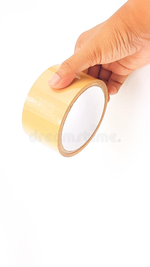 Man hand holding thick brown plastic tape with big core. Isolated royalty free stock photos