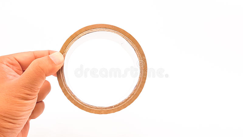Man hand holding thick brown plastic tape with big core. Isolated stock photos