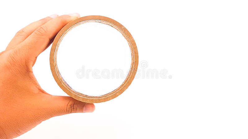 Man hand holding thick brown plastic tape with big core. Isolated stock photo