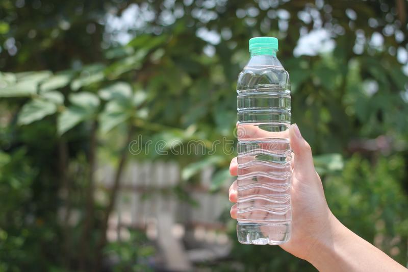 The man hand holds a bottle of drinking water. In the garden and have copy space for you stock photography