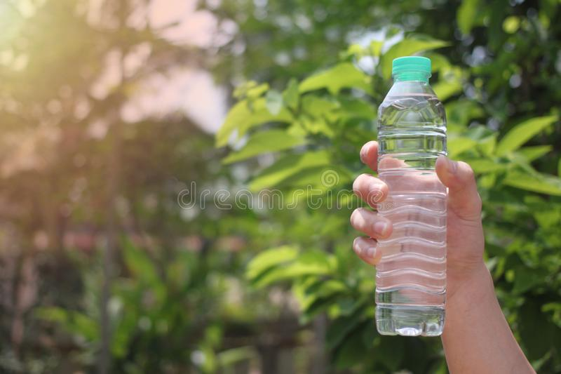 The man hand holds a bottle of drinking water. In the garden and have copy space for you royalty free stock photo