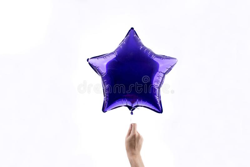 Man hand holds a purple flying balloon in the shape of a star isolated on white background royalty free stock images