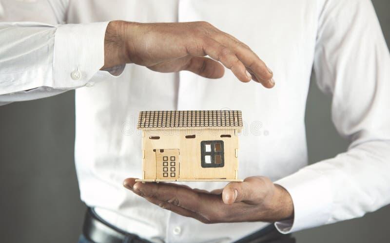 Man hand house model. On dark background stock image