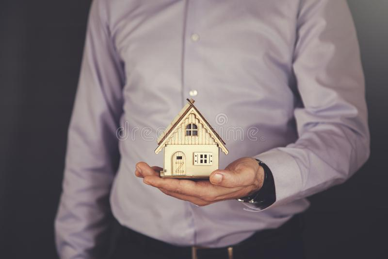 Man hand house model. Young business man hand holding house model stock photo