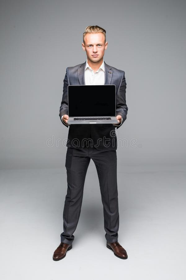 Man hand on laptop with blank screen monitor for text. Businessman showing laptop with blank screen. Businessman standing posture. Man hand on laptop with blank stock photography