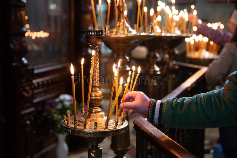 Man hand lighting candles in a church royalty free stock photography