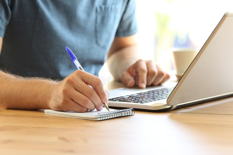 Man hand on line taking notes in a notebook royalty free stock photography
