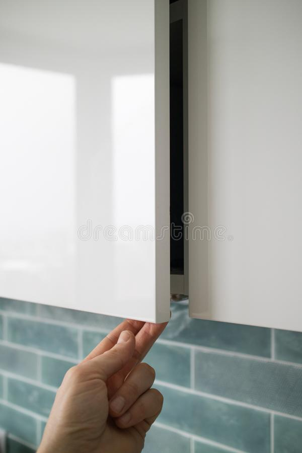 Man hand opening or closing kitchen cabinet door. The closeup man hand opening or closing kitchen cabinet door on a background of blue kitchen interior. Modern stock image