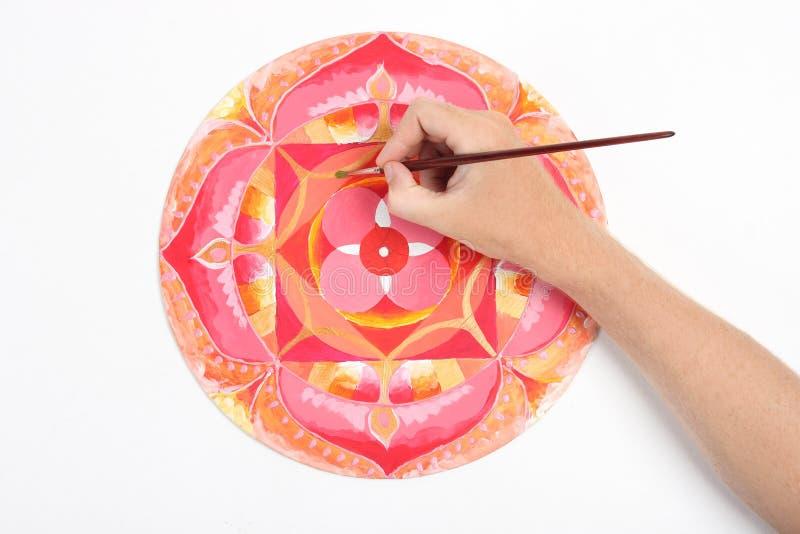 Man hand painting abstract red picture. With circle pattern, mandala of muladhara chakra royalty free stock photos