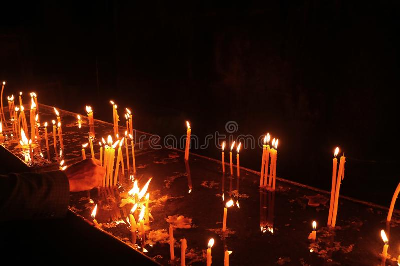 Man Hand Placing Lit Candle into the Votive Candle Stand inside the Church. Archaeological site in Armenia royalty free stock photos