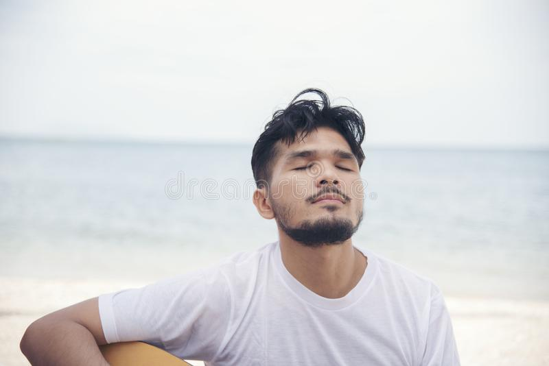Man hand playing guitar on the beach. Acoustic musician playing  classic guitar. Musical Concept. Man hand playing guitar on the beach. Acoustic musician playing royalty free stock photography