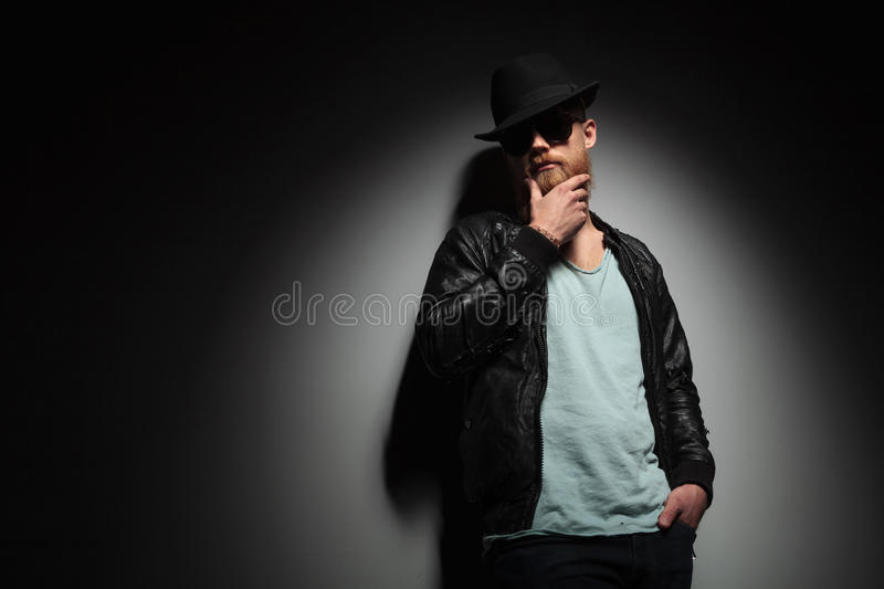 Man with hand in pocket caresses beard stock photography
