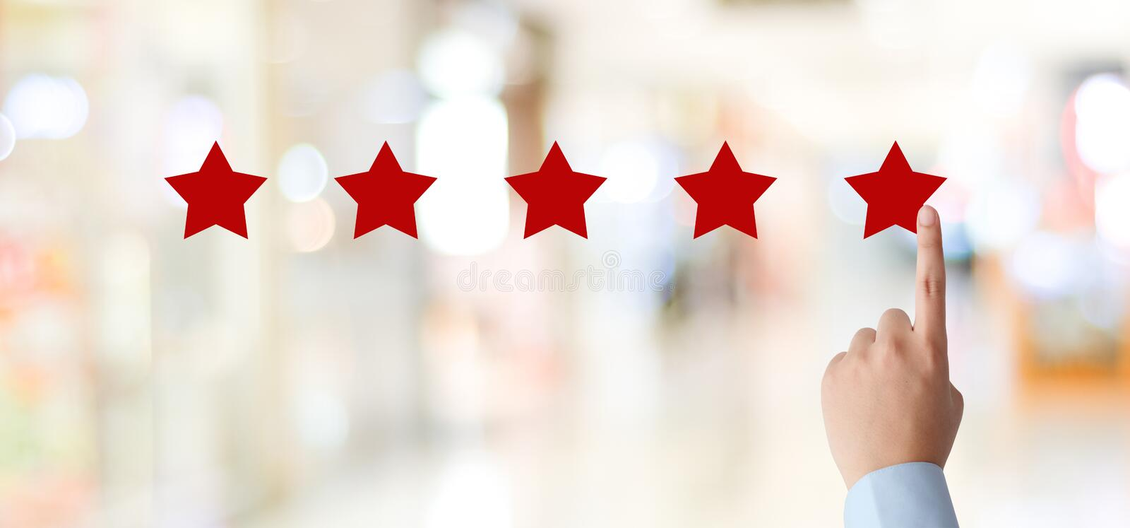 Man hand pointing red five star over blur background, customer excellent rating satisfacation, customer feedback, business concept royalty free stock images