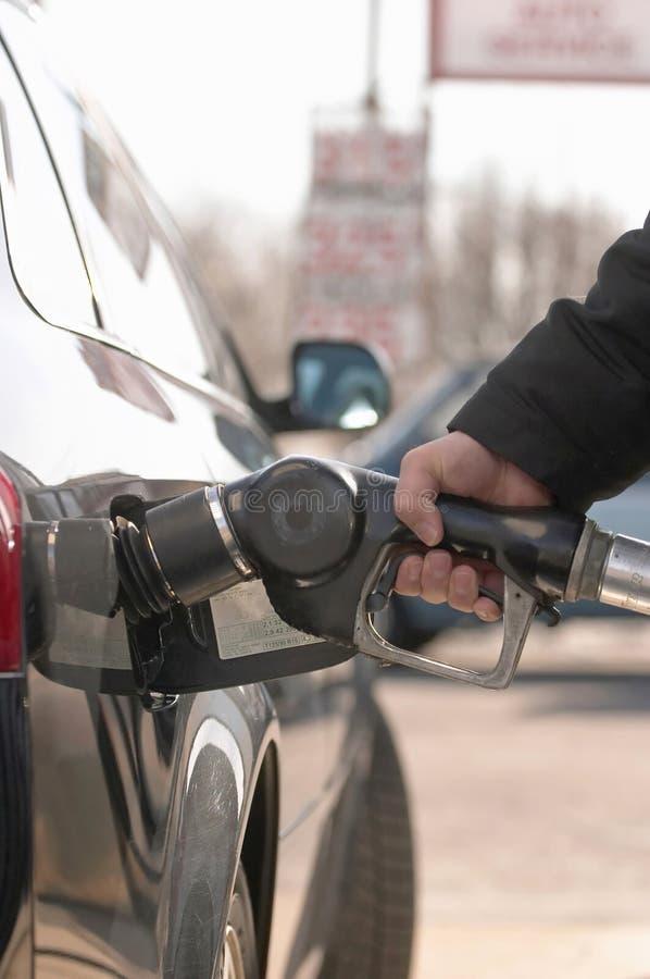 Man hand pompend gas in auto stock afbeeldingen