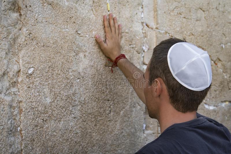 Man hand and pray paper on the Western Wall, Wailing Wall the Place of Weeping is an ancient limestone wall in the Old City of. Jerusalem. Second Jewish Temple royalty free stock photo