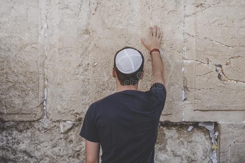 Man hand and pray paper on the Western Wall, Wailing Wall the Place of Weeping is an ancient limestone wall in the Old City of. Jerusalem. Second Jewish Temple stock image