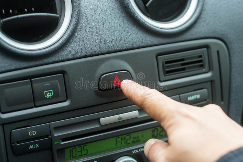 Man Hand Pressing Car Hazard Lights Button royalty free stock photos