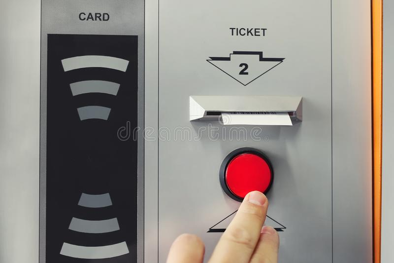 Man hand pushing red button to recieve ticket at car parking entrance. Ticket printing terminal machine with wireless card access royalty free stock photography