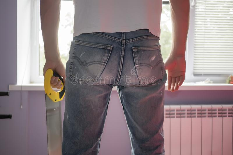 Man with hand saw in old dirty jeans stands at the window royalty free stock images