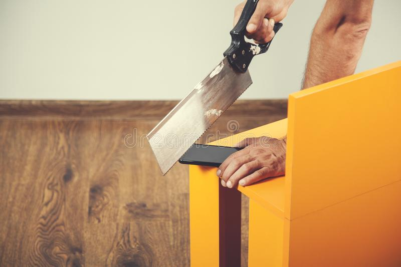 Man hand saws with phone royalty free stock photo