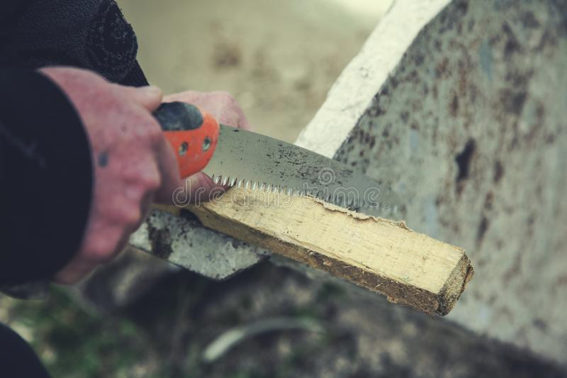 Man hand saws with wood royalty free stock image