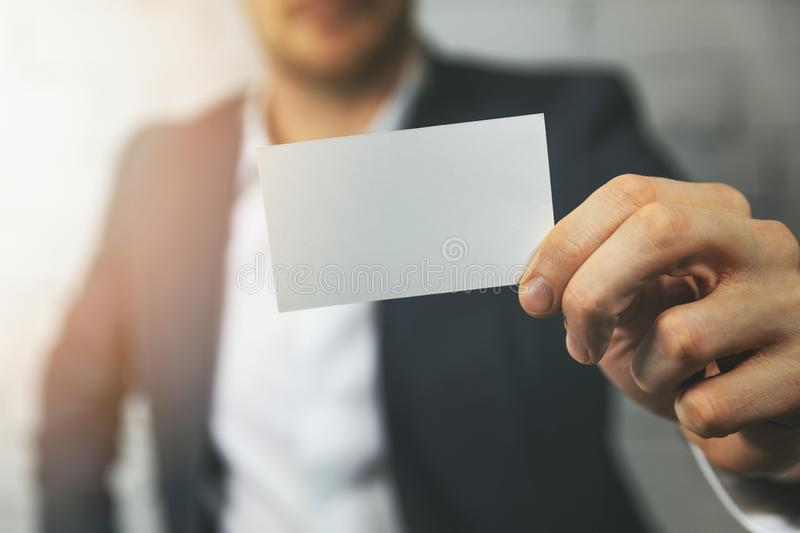 Man hand showing blank business card in front stock photography