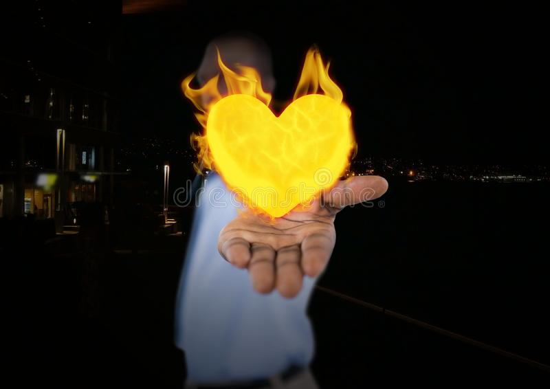 Man with hand spread of with heart fire icon over. City at night royalty free stock images