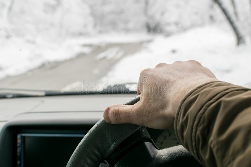 Man hand on the steering wheel of a car that moves in the snowy forest on a wet slushy road. Man`s hand on the steering wheel of a car that moves in the snowy stock photos