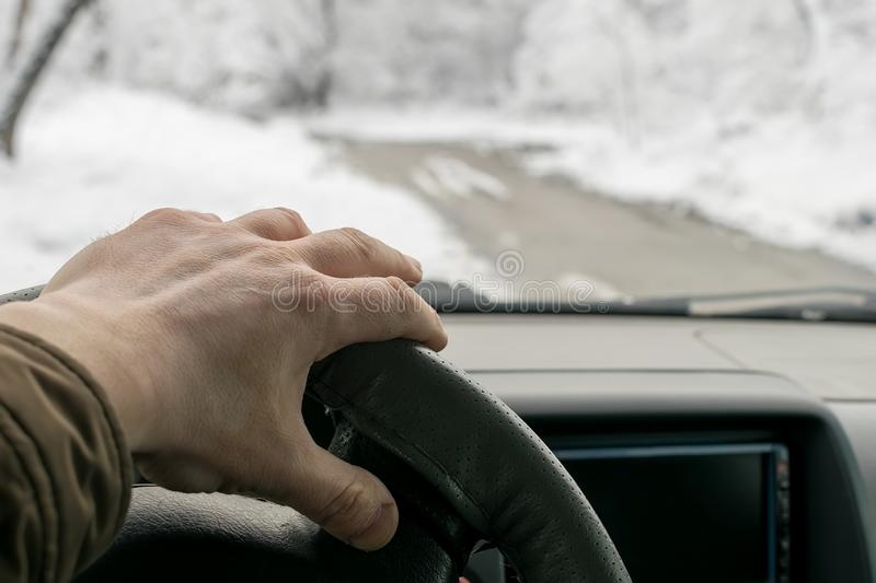 Man hand on the steering wheel of a car that moves in the snowy forest on a wet slushy road. Man`s hand on the steering wheel of a car that moves in the snowy royalty free stock photos