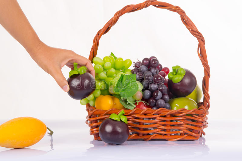 Man hand taking mangosteen in a fresh fruit basket. royalty free stock photo