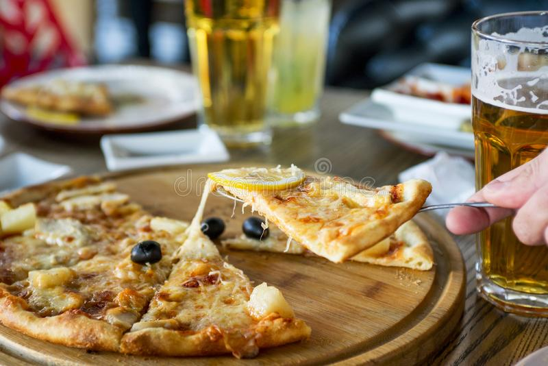 Man hand taking slice of pizza from wooden board. People eat fast food in cafe stock image