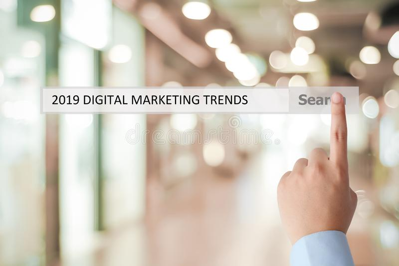 Man hand touching 2019 digital marketing trends on search bar over blur office background, banner, 2019 business strategy annual stock photos
