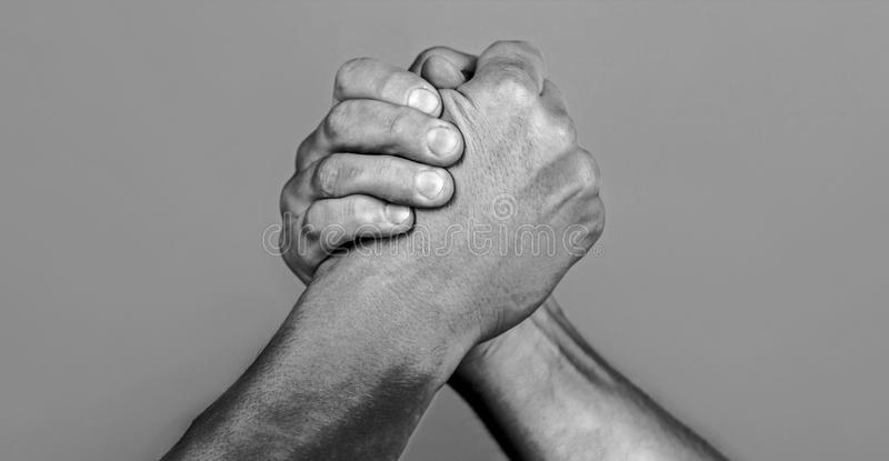 Man hand. Two men arm wrestling. Arms wrestling. Closep up. Friendly handshake, friends greeting, teamwork, friendship. Handshake, arms, friendship Hand royalty free stock photos