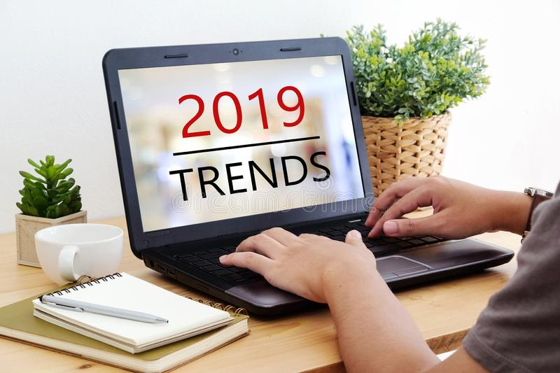 Man hand tying laptop computer with 2019 trends on screen background, digital marketing, business and technology concept stock images