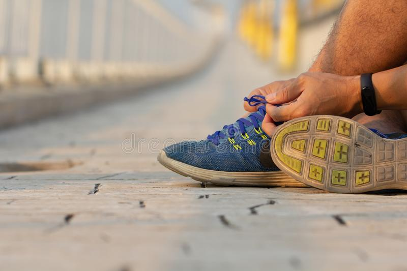 Man hand tying sport shoe laces in casual clothes after workout..Young fitness man running outside city. People fitness, exercise. royalty free stock image