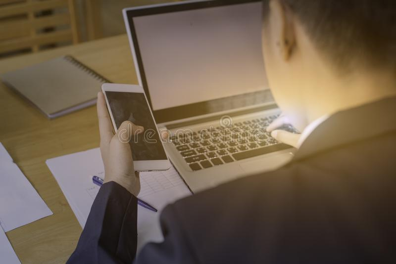 Man hand using mobile phone with laptop on wood table with sheet. Side view shot of a man`s hands using smart phone in interior, rear view of business man hands stock photo
