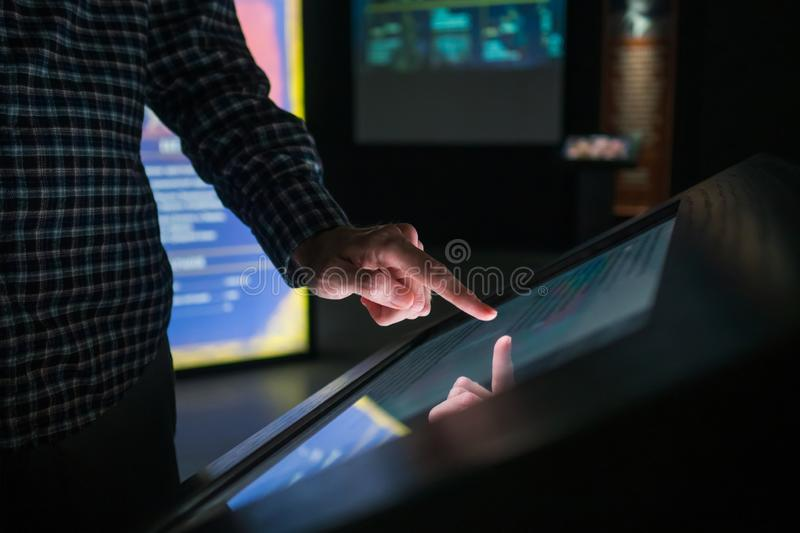 Man hand using multimedia touchscreen display of interactive kiosk at exhibition. Man hand using interactive touchscreen display of electronic multimedia stock image
