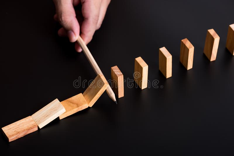man hand using a pen stop domino falling effect on black background ,using idea to solve the problem stock photo