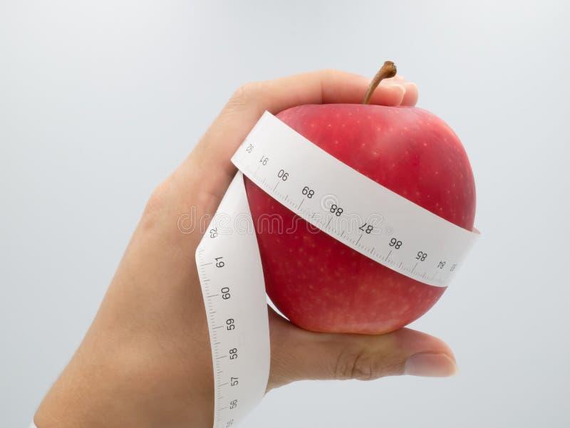 Man hand verse rode appel houden die spiraalvormig die wapen en hand die met het meten van banddieet en gezondheidszorgconcept, o royalty-vrije stock foto
