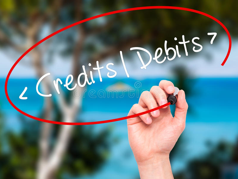 Man Hand writing Credits - Debits with black marker on visual sc. Man Hand writing Credits - Debitswith black marker on visual screen. Isolated on background royalty free stock photography