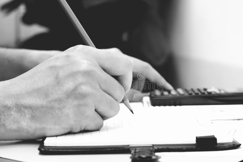 Man hand is writing in a notebook and calculator counting making royalty free stock photography