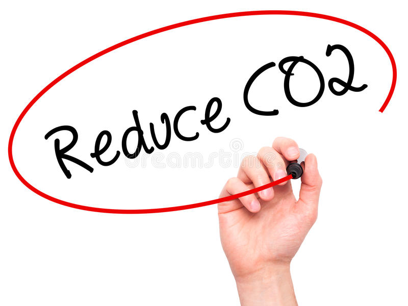 Man Hand writing Reduce CO2 with black marker on visual screen. stock photo