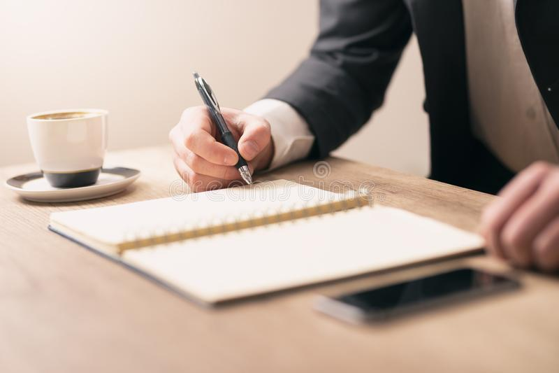 Man hand writing something on notebook stock photos