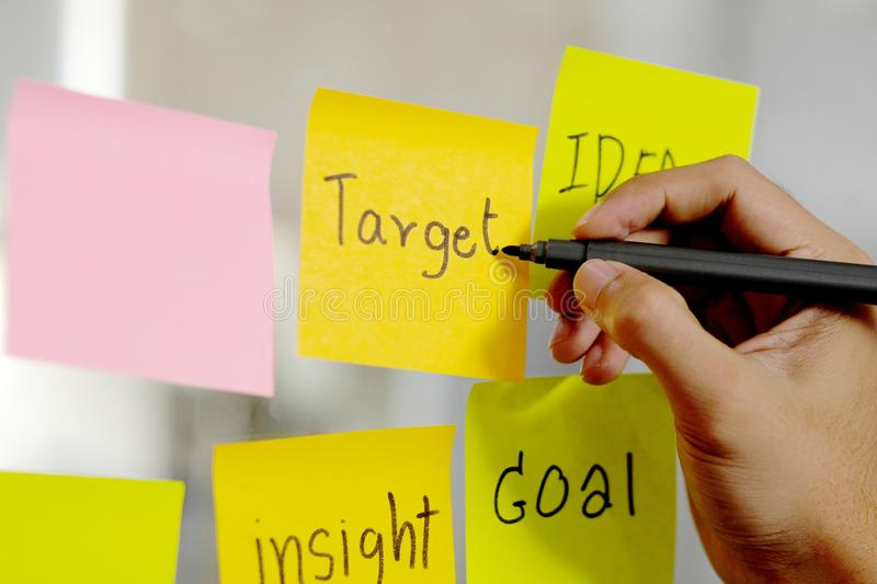 Man hand writing target word on sticky note at office, Close up of target and business idea words on adhesive note, Brainstorming. Business strategy planing stock photos