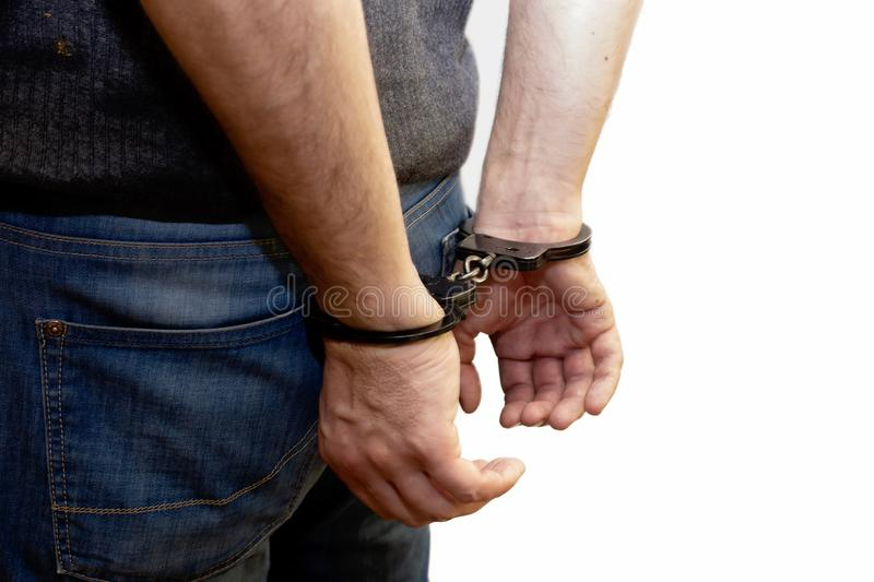 The man is handcuffed, his hands behind his back, the caught criminal stock photos
