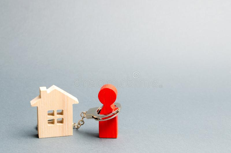 The man is handcuffed to a wooden house. The concept of restriction of freedom due to non-payment of property taxes or mortgage. Loans. Debt load for housing stock photography