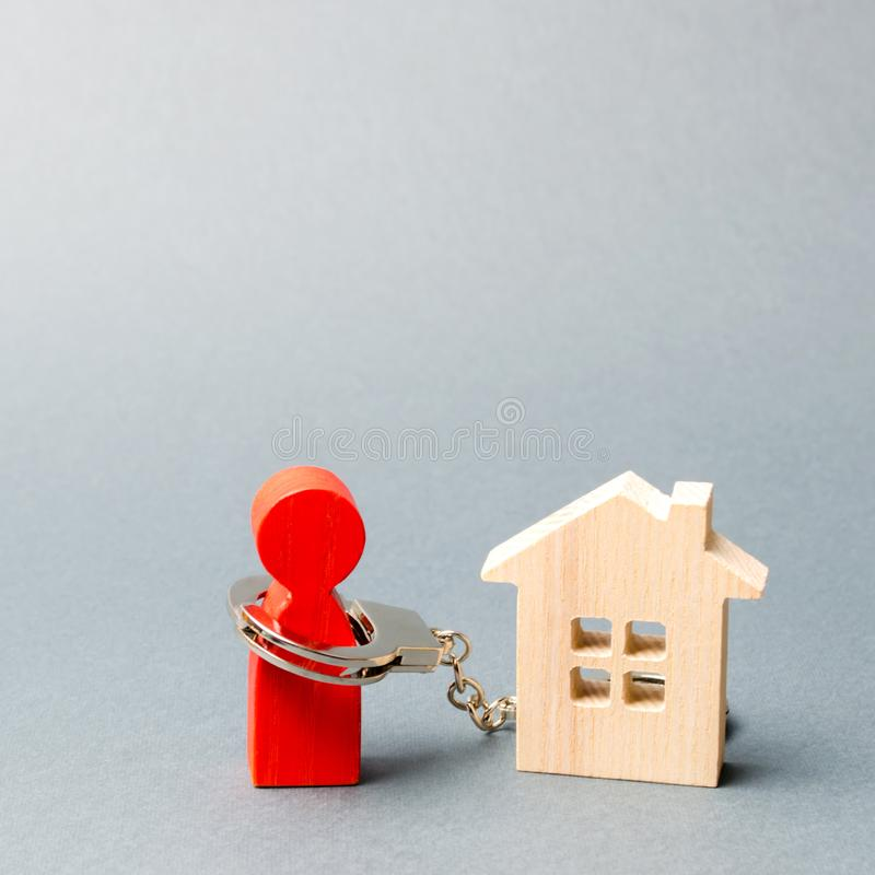 The man is handcuffed to a wooden house. The concept of restriction of freedom due to non-payment of property taxes or mortgage. Loans. Debt load for housing royalty free stock photo