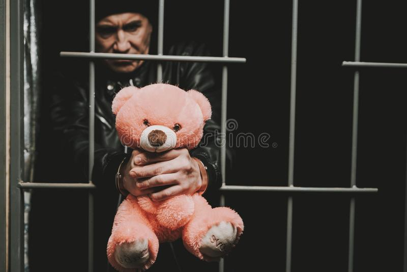 Man In Handcuffs Behind Bars In A Police Station. stock image