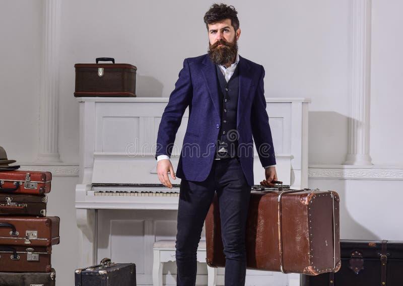 Man, handelsresande med skägget och mustasch med bagage, lyxig vit inre bakgrund Bagage och resande begrepp fotografering för bildbyråer
